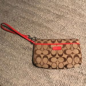 Coach wristlet with red detailing